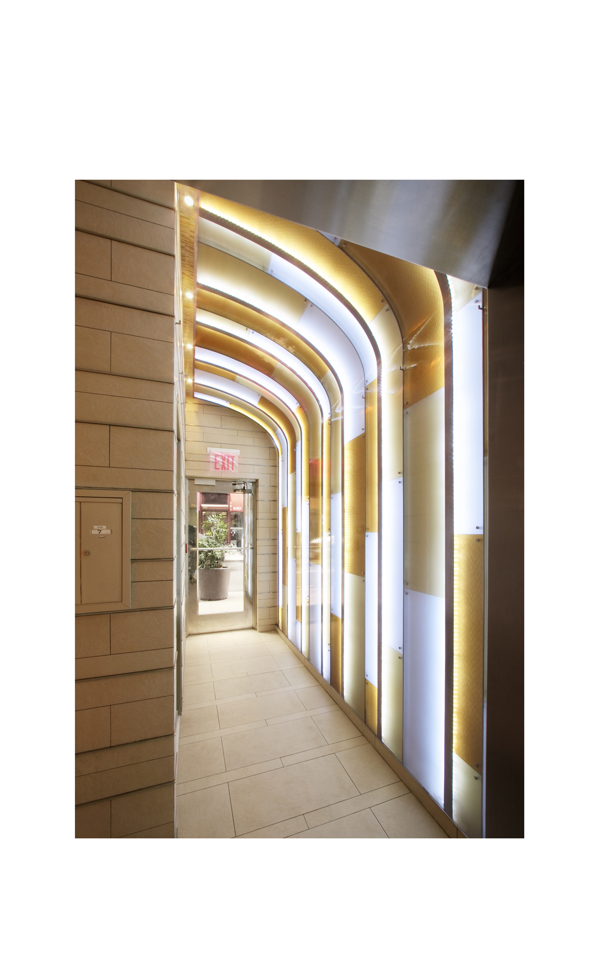The glowing arched wall is illuminated by concealed leds light filtering through the patterned glass creates depth brightness and enhances the illusion of